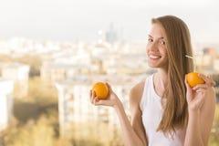 Spielerische Frau, die Orangensaft trinkt Stockfotografie