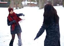 Spielerische Frauen, die draußen im Schnee spielen Stockfotos