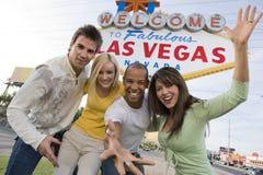 """Spielerische Freunde, die zusammen gegen """"Willkommen nach Las Vegas"""" Zeichen stehen Stockbilder"""
