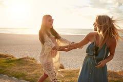 Spielerische Freundinnen auf einem Bürgersteig entlang dem Strand stockfotografie