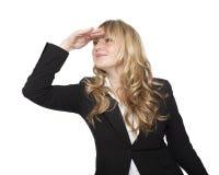 Spielerische Geschäftsfrau, die in den Abstand blickt Stockbilder