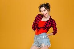 Spielerische glückliche Stellung und Blinzeln der jungen Frau Lizenzfreie Stockbilder
