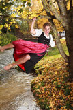 Spielerische junge Frau, die auf einem Baum schwingt Lizenzfreie Stockfotos
