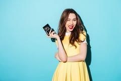 Spielerische junge Frau im Kleid, das Retro- Kamera und das Blinzeln hält Lizenzfreies Stockbild
