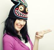 Spielerische junge Frau im lustigen Hut mit Kaninchen Lizenzfreie Stockbilder