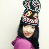 Spielerische junge Frau im lustigen Hut mit Kaninchen Stockbild