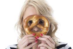 Spielerische junge Frau mit Frühstücks-Brezel über Gesichts-Augen durch lugend Lizenzfreies Stockbild