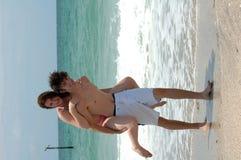 Spielerische junge Strandpaare stockfotos