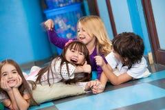 Spielerische Kinder, die auf Boden liegen Lizenzfreie Stockfotos
