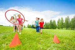 Spielerische Kinder, die bunte Bänder auf Kegeln werfen Stockfotografie