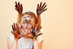 Spielerische Mädchen mit den farbigen Händen stockfotografie