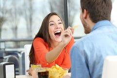 Spielerische Paare, die Bratkartoffeln essen stockbild