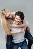 Spielerische Paare, die piggyback zusammen reiten Lizenzfreie Stockbilder