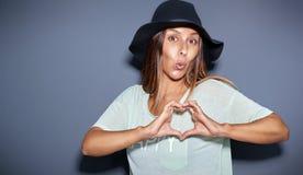 Spielerische romantische junge Frau, die ein Herzzeichen macht Lizenzfreie Stockbilder