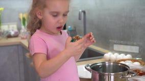 Spielerischer Blick des kleinen Mädchens auf gemalte Eier und vor Kamera geziert lächeln Kardanring stock video