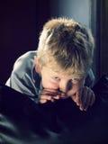 Spielerischer blonder Junge, der Kamera betrachtet Lizenzfreies Stockfoto