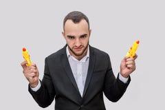 Spielerischer junger Mann im Klagenstand und -blick auf Kamera Er wirft auf Kerl hält zwei gelbe Wasserpistolen Er ist verärgert  stockfotos