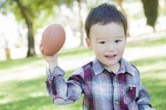 Spielerischer junger Mischrasse-Junge, der draußen Fußball spielt Stockfotografie