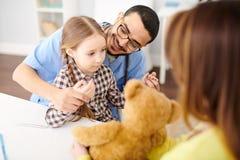 Spielerischer Kinderarzt Working mit kleinem Mädchen lizenzfreie stockbilder