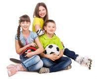 Spielerischer kleiner Junge und Mädchen, die auf dem Boden sitzen Stockfotos