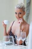 Spielerischer sexy blonder trinkender Kaffee, Nahaufnahme Lizenzfreie Stockfotos