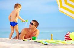 Spielerischer Sohn streut Sand auf Vater, Strand Lizenzfreies Stockfoto