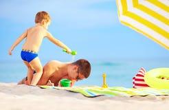 Spielerischer Sohn streut Sand auf Vater, Strand Lizenzfreie Stockbilder