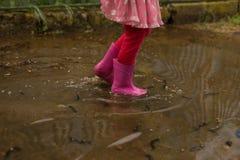 Spielerischer Sprung des kleinen Mädchens im Freien in Pfütze im rosa Stiefel nach Regen Haus gebildet vom Geld im schwarzen Hint lizenzfreies stockbild