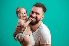 Spielerischer Vater, der sein lächelndes Säuglingskind auf Hals über blauem Hintergrund trägt stockfoto