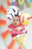 Spielerisches Baby, das oben zu seinen Spielwaren in seiner Krippe lacht und schaut Lizenzfreies Stockbild
