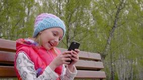 Spielerisches Jugendlichmädchen, welches das intelligente Telefon im Frühjahr sitzt auf Stadtpark der Bank verwendet stock footage