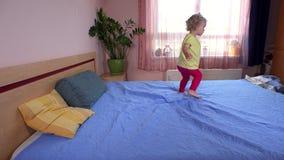 Spielerisches Kind des kleinen Mädchens springen und laufen auf Schlafzimmerbett stock footage