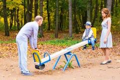 Spielerisches Kind mit Eltern am Spielplatz im Freien Mamma, Vati und Schätzchen Stockfotografie