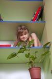 Spielerisches kleines Mädchen, das auf dem Regal sich versteckt Lizenzfreie Stockbilder