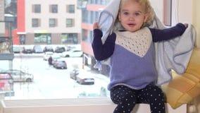 Spielerisches Mädchen mit Tuch auf ihrem Haar, das auf Heizkörper nahe Fenster sitzt schneesturm stock footage