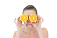 Spielerisches natürliches braunes behaartes Modell, das ihre Augen hinter orange Hälften versteckt Lizenzfreie Stockbilder