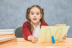 Spielerisches nettes kleines Mädchen, das Spaß beim Lehnen auf starken Büchern auf dem grauen Hintergrund hat Ihr Haar wird in de lizenzfreie stockfotografie