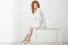 Spielerisches recht zartes Mädchen mit dem gelockten roten Haar lachend, das Sitzen auf Tabelle über weißem Hintergrund aufwerfen Stockbild