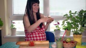 Spielerisches schwangeres Mädchen, das Kamera mit Lächeln betrachtet und Bonbons isst stock video