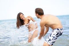 Spielerisches Spritzwasser der Strandsommerspaß-Paare Stockfoto