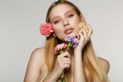 Spielerisches und sexy Porträt der hübschen netten Frau mit Frühlingsblumen nahe ihrem Gesicht stockfoto