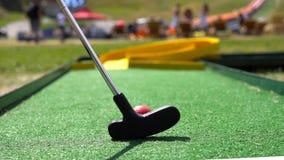 Spielerspiel-Minigolf mit rotem Ball stockfotos
