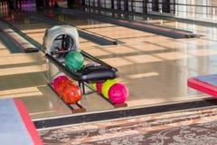 Spielfeld in der Bowlingbahn mit Bowlingkugeln auf Vordergrund Stockfotografie