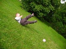 Spielfußball des kleinen Jungen Lizenzfreie Stockfotos