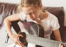 Spielgitarre des kleinen Mädchens lizenzfreies stockbild