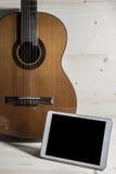 Spielgitarre Lieder die Tablette Lizenzfreie Stockfotografie