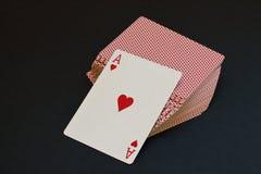 Spielkarte mit rotem Herzen als ursprünglicher stilisierter Grußkarte für Valentinstag auf Kartenstapel auf schwarzem Hintergrund lizenzfreie stockbilder
