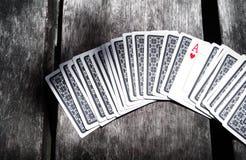Spielkarteas auf einem Holztisch lizenzfreie stockfotos