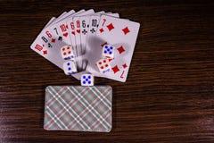Spielkarten auf dem dunklen Holztisch Beschneidungspfad eingeschlossen stockbilder
