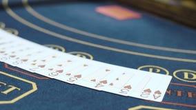 Spielkarten breiteten in der Reihe auf Tabelle aus, bevor sie Schürhaken spielten Spielen im Kasino stock video